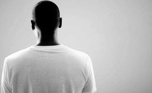 A still from the art film #Blackmendream. The film features nine men, turned away from the camera and talking about their hopes and fears.
