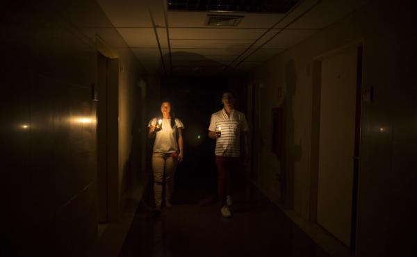 Amid a widespread power outage in Venezuela on Thursday, relatives of a patient walk in the dark halls of a health clinic in Caracas.