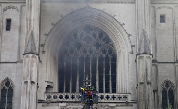 Firefighters work to extinguish the blaze at the Cathedral of St. Peter and St. Paul in Nantes on Saturday. The fire shattered stained-glass windows and sent black smoke billowing from between its two towers.