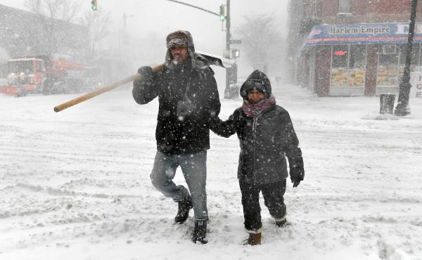 Pedestrians cross the street in Harlem during a snow storm. As a major winter storm moves up the Northeast corridor, New York City is under a winter storm warning.