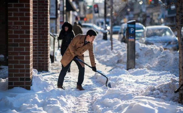 A man shovels snow from a footpath in New York City.