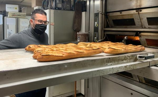 Tony Doré wears a face mask as baguettes cool in his bakery in Paris' 15th arrondissement.