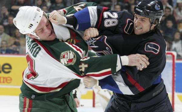 Derek Boogaard of the Minnesota Wild (left) and Wade Brookbank of the Vancouver Canucks exchange punches during a fight in the first period of a November 2005 game in Vancouver, Canada.