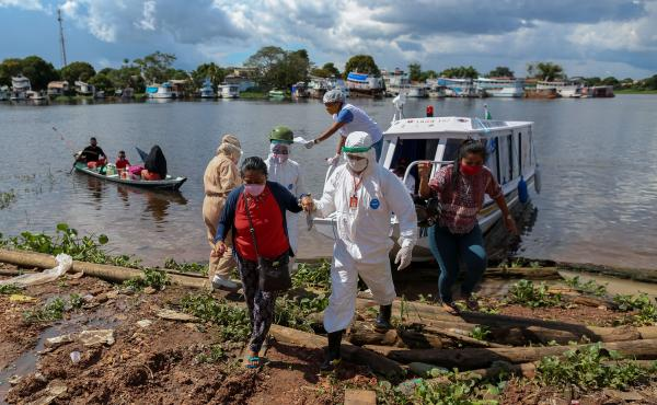 A surge in cases and record high daily death tolls have pushed Brazil into a COVID crisis. Above: Health professionals help patients with symptoms of the new coronavirus on a boat ambulance.