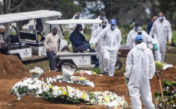 Several COVID-19 burials are performed in the Vila Formosa Cemetery on the east side of São Paulo, Brazil, on Sunday. Brazil, which reported a large spike in cases on Monday, now ranks second after the U.S. for total infections and deaths.