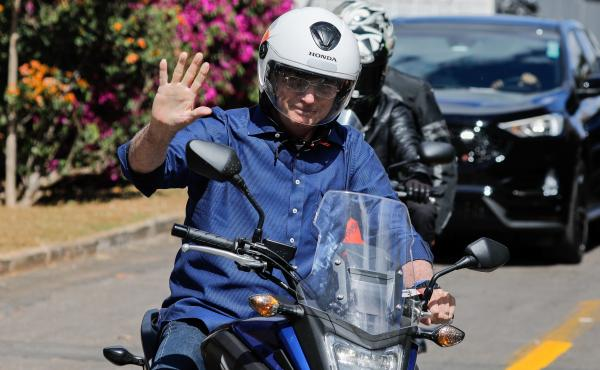 Brazilian President Jair Bolsonaro takes a ride on a motorcycle Saturday in Brasilia after he announced he tested negative for the coronavirus. He had tested positive earlier this month.