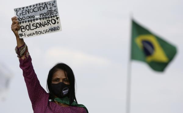 "A women's movement activist holds a sign that reads in Portuguese ""Genocide 60 thousand deaths, Bolsonaro out,"" during a protest against the government's handling of the pandemic earlier this month."