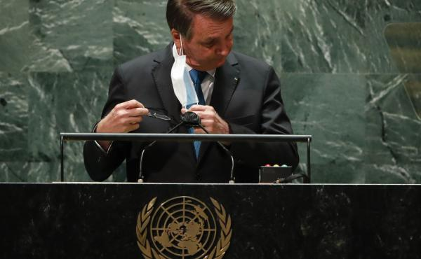 Brazilian President Jair Bolsonaro pulls off his protective face mask to address the 76th session of the U.N. General Assembly at United Nations headquarters in New York on Tuesday.
