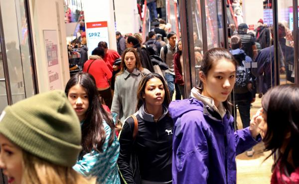 Shoppers walk out of Uniqlo on 5th Ave. in New York City on Black Friday, Nov. 27.
