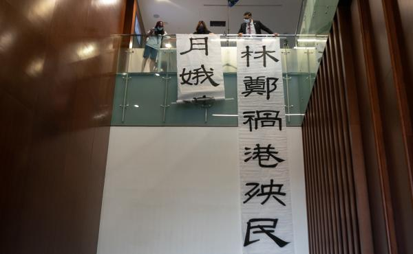 Pro-democracy lawmaker Lam Cheuk-ting hangs banners during a session at the Legislative Council outside of the main chamber on Thursday in Hong Kong. Fifteen pro-democracy lawmakers resigned en masse after four colleagues were disqualified from serving.
