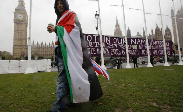 A man wears a Palestinian and Union flag outside the Houses of Parliament in London on Monday to show his support for the symbolic vote.