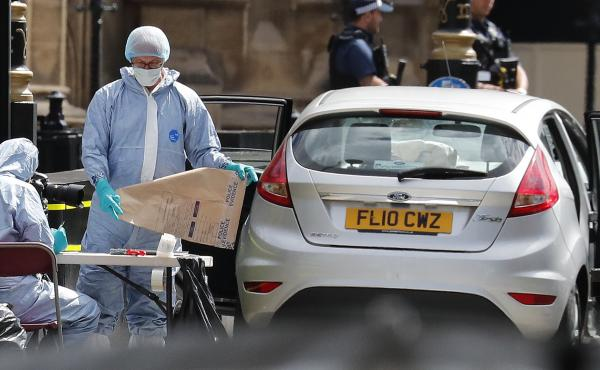 Forensics officers work near the car that crashed into security barriers outside the Houses of Parliament in London on Tuesday. British media report that Salih Khater has been arrested on charges of terrorism.