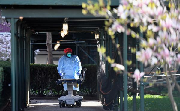 A medical staff member wearing personal protective equipment pushes an empty gurney at Kingsbrook Jewish Medical Center in Brooklyn on April 8. Nurses who gathered in protest outside Kingsbrook earlier this week said a shortage of protective gear at their