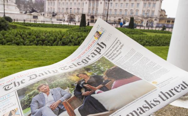 A British newspaper flutters in the wind outside Buckingham Palace in London the day after the Duke and Duchess of Sussex's interview with Oprah Winfrey.