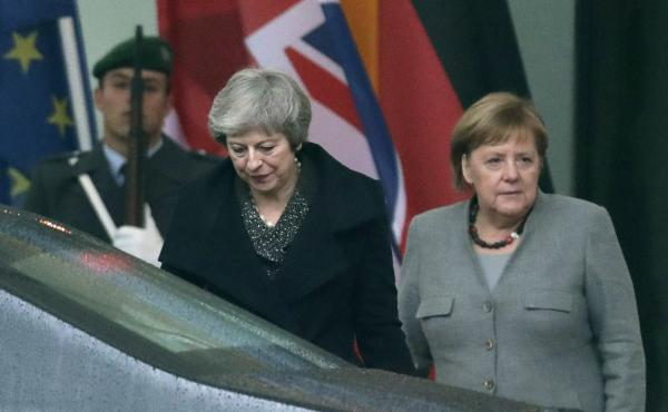 British Prime Minister Theresa May (center) leaves a meeting Tuesday in Berlin beside German Chancellor Angela Merkel. Faced with turmoil back home, May has embarked on an international trip to shore up assurances from the European Union.