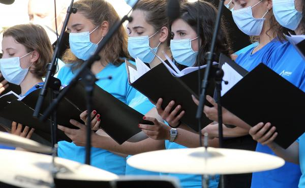 The Centers for Disease Control and Prevention briefly posted new guidance to its website stating that the coronavirus can commonly be transmitted through aerosol particles, which can be produced by activities like singing. Here, choristers wear face mask