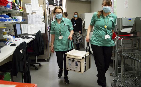 On Wednesday, pharmacists at the West Wales General Hospital in Carmarthen, Wales, transport a cool box containing the first batch of Moderna vaccines being distributed in Britain.