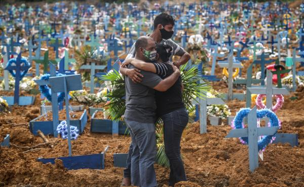 Relatives at a mass burial of pandemic victims at the Parque Taruma cemetery in Manaus, Brazil, mourn a family member.
