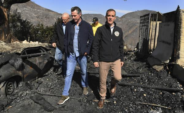 From left, LA City Councilman Mike Bonin, California Gov. Gavin Newsom and LA Mayor Eric Garcetti tour a burned home along in Brentwood, Calif., on Tuesday.