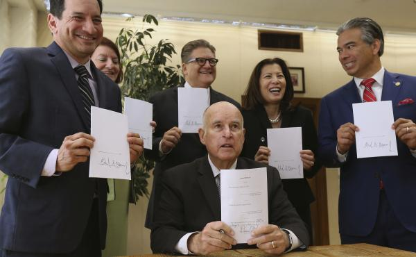 Gov. Jerry Brown holds a copy of a bill to end bail he signed Tuesday, Aug. 28, in Sacramento, Calif. The bill, co-authored by state Sen. Bob Hertzberg, D-Van Nuys, third from right, and Assemblyman Rob Bonta, D-Alameda, right, makes California the first