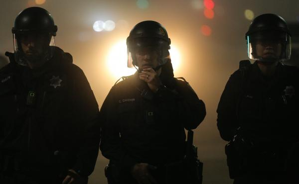 Oakland police officers, wearing body cameras, form a line during demonstrations against recent incidents of alleged police brutality nationwide.