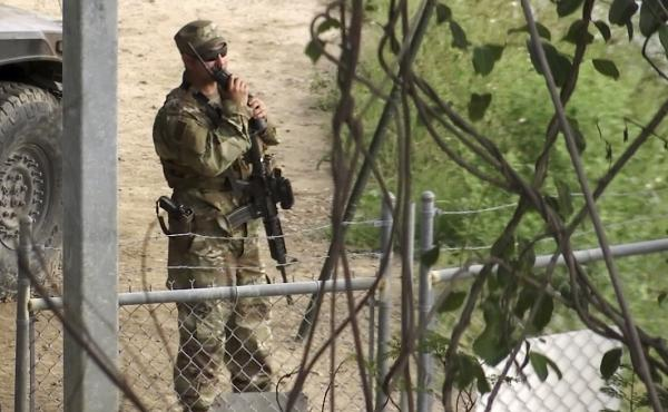 In this frame from a video, a member of the National Guard watches over Rio Grande River on the border in Roma, Texas, on Tuesday. The deployment of National Guard members to the U.S.-Mexico border at President Trump's request was underway Tuesday with a