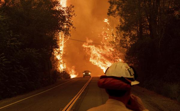 A car passes through flames on Highway 299 as the Carr Fire burns through Shasta, California, on July 26. Fueled by high temperatures, wind and low humidity, the blaze has destroyed multiple structures and killed seven people.