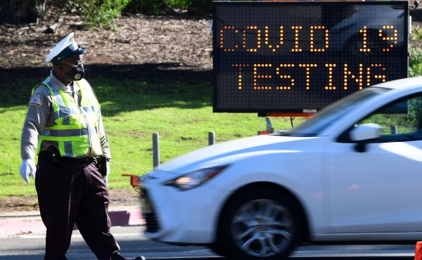 A traffic warden directs traffic as people arrive and depart from the coronavirus testing venue at Dodger Stadium in Los Angeles on Thursday.