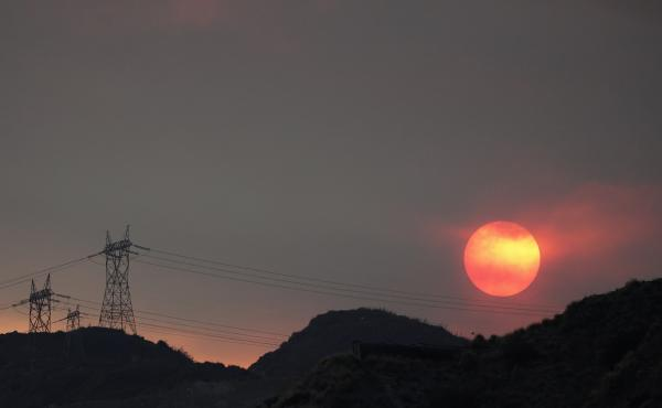 The sun sets through smoke created by the Ranch Fire this week in Azusa, Calif. The heat wave will likely hinder firefighting efforts, but at least the strong winds that fuel wildfires are not expected.