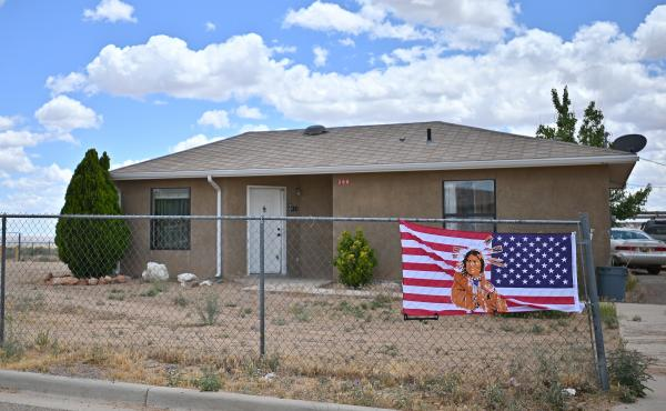 An American flag with an image of a Native American on it in To'Hajiilee Indian Reservation in New Mexico. In California, a vaccine allocation committee is considering taking historical injustice into account in advance of a statewide rollout.
