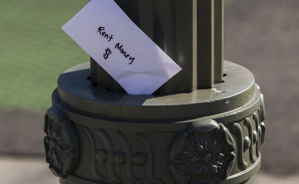 "A paper envelope written with the words ""Rent Money $"" is left tucked in a lighting pole in April in the Boyle Heights area of Los Angeles. Amid massive job losses due to COVID-19, California Gov. Gavin Newsom signed an extended eviction moratorium on Mon"