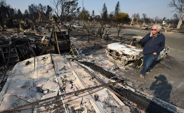 Homeowner Phil Rush is confronted by the remains of his home that was destroyed by wildfire in Santa Rosa, Calif. He says he and his wife and dog escaped with only their medication and a bag of dog food when flames overtook their neighborhood.