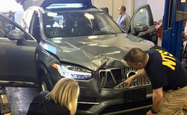 Investigators for the National Transportation Safety Board in Tempe, Ariz., examine the Uber vehicle involved in the fatal crash.