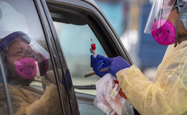 A member of the AltaMed Health Services staff prepares to take a sample at a drive-through coronavirus testing site in Los Angeles.