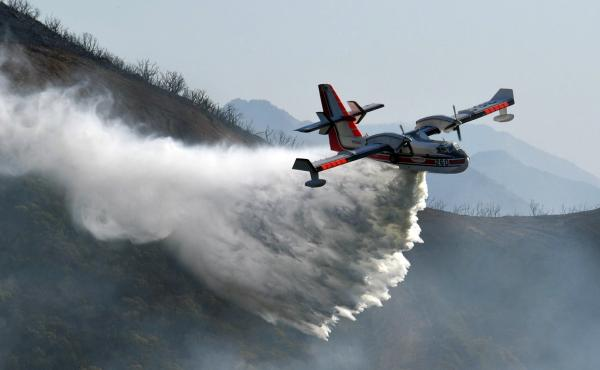 In this photo provided by the Santa Barbara County Fire Department, a Bombardier 415 Super Scooper makes a water drop on hot spots along the hillside east of Gibraltar Road in Santa Barbara, Calif., on Sunday morning.
