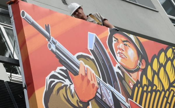 Workers remove a poster for The Interview from a billboard in Hollywood, Calif., after Sony canceled the movie's Christmas release due to a terrorist threat. The hacking of Sony's networks has sparked a war of words between the U.S. and North Korea.