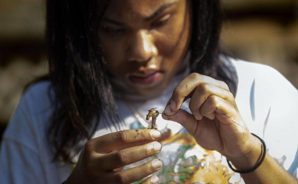 Alaysia Mondon, 14, baits her hook with a worm while fishing on Lake Lashaway.