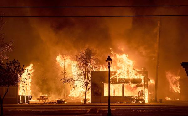 Buildings are engulfed in flames as a wildfire ravages Talent, Ore., on Sept. 8, 2020. Unfounded rumors that left-wing activists were behind the fires went viral on social media, thanks to amplification by conspiracy theorists and the platforms' own desig