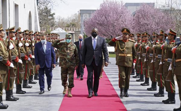 U.S. Defense Secretary Lloyd Austin, center, walks on the red carpet with Afghan officials as they review an honor guard at the presidential palace in Kabul, Afghanistan, on March 21. President Biden said the U.S. will withdraw all remaining troops from t