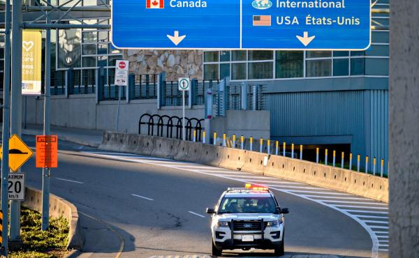 Canada plans to impose a new vaccine mandate on passengers and workers in the federally regulated air, rail and cruise ship sectors. Here, a police car is seen behind traffic cones in May near Vancouver International Airport in British Columbia.