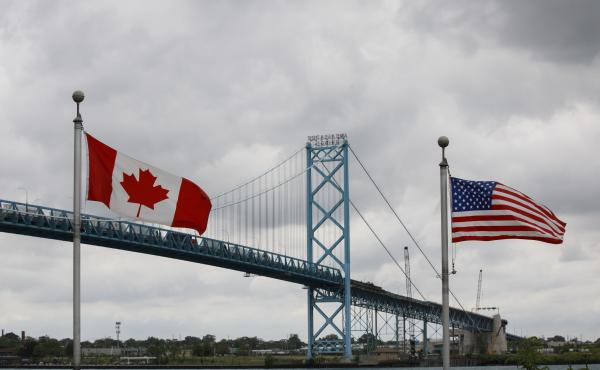 Canadian and American flags fly near the Ambassador Bridge connecting Canada to the U.S. in Windsor, Ontario, in May. Half of respondents in a poll of Canadians this month by Nanos Research said restrictions on travel across the U.S.-Canada border should