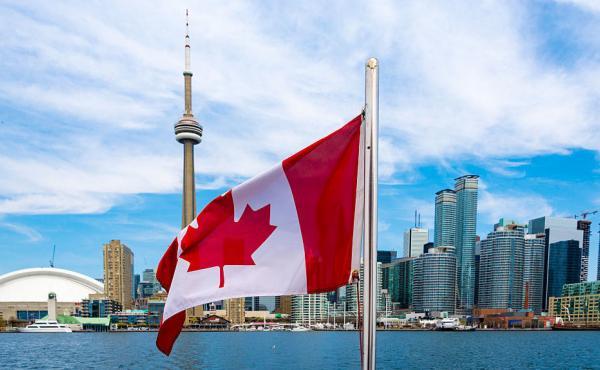 Canadian flag and the Toronto skyline.