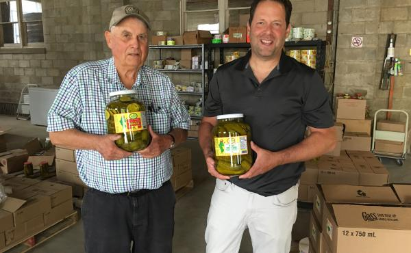 Don Woodbridge (left) and son Alan Woodbridge hold jars of pickles at their company in Harrow, Ontario. Orders are up in anticipation of retaliatory Canadian tariffs on U.S. gherkins.