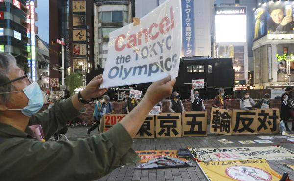 A demonstrator holds a placard during an anti-Olympics demonstration in Tokyo on Monday. A prominent doctors association has joined calls to cancel the Summer Games in Tokyo.