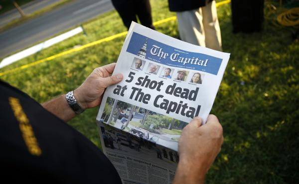 Steve Schuh, county executive of Anne Arundel County, holds a copy of The Capital newspaper last month near the scene of a shooting at the Capital Gazette newsroom in Annapolis, Md.