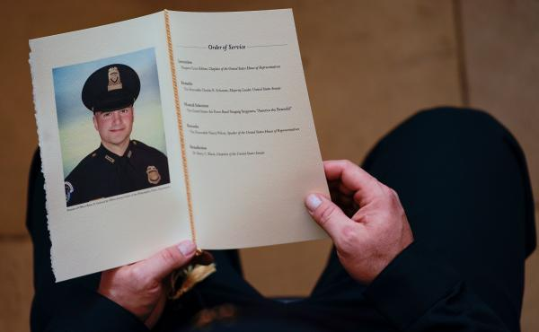 A U.S. Capitol Police officer holds a program during a Feb. 3 ceremony honoring Brian Sicknick in the Capitol Rotunda. A medical examiner determined that Sicknick died of natural causes following the Jan. 6 insurrection.