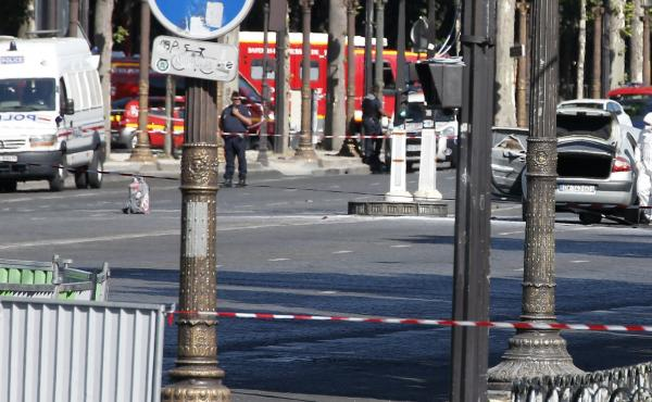 Police search a white car (right) that had been rammed into a police van on the Champs-Élysées in Paris on Monday afternoon.