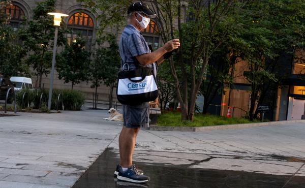 A Census Bureau worker with a face covering stands in a park in New York City in August. The bureau confirmed on Tuesday that door knocking is ending in some areas earlier than Sept. 30.