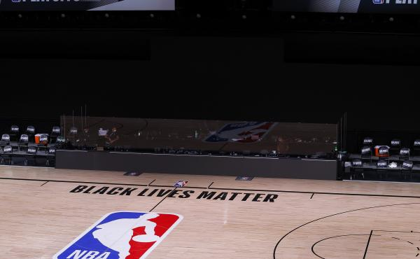 An empty court and bench are shown with no signage following the scheduled start time of Wednesday's NBA playoff series. NBA players made their strongest statement yet against racial injustice Wednesday when the Milwaukee Bucks didn't take the floor for t