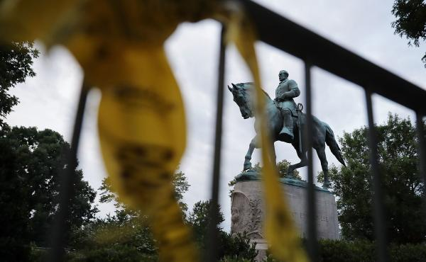 """The statue of Confederate Gen. Robert E. Lee stands in the center of Emancipation Park the day after violence broke out in Charlottesville, Va. The """"Unite the Right"""" rally aimed to save the statue, which the city council has voted to remove. But several c"""